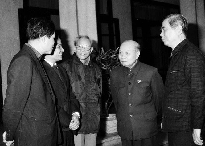 Ông Trường Chinh và ông Nguyễn Văn Linh trò chuyện với các thành viên trong ban soạn thảo văn kiện Đại hội VI, tháng 11-1986 - Ảnh: Xuân Lâm
