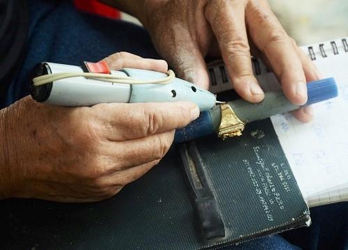 Ông Dũng có thể khắc chữ lên rất nhiều chất liệu với 8 cây bút tự chế. Ảnh: Mỹ Phượng.