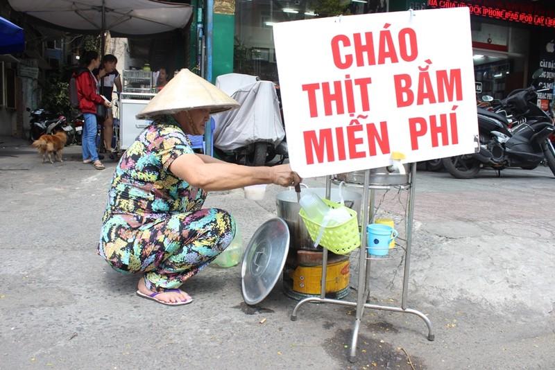 """Cô Từ Bình (64 tuổi, quận 10) là khách quen của """"Cháo thịt bằm miễn phí"""". Khi lấy suất cháo cho mình, cô Bình luôn nhớ chuẩn bị thêm 2-3 phần cho những cụ già khác trong xóm. Thay vì dùng hộp nhựa ở đây, cô thường tự mang hộp nhựa đến để đựng cháo, coi như cách tiết kiệm và trả ơn cô Linh vậy."""