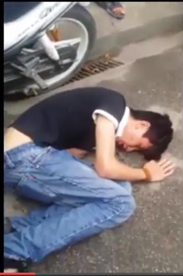 Nam thanh niên vi phạm giao thông bị đánh gãy răng cửa, ngất lim trên đường. Ảnh cắt từ clip
