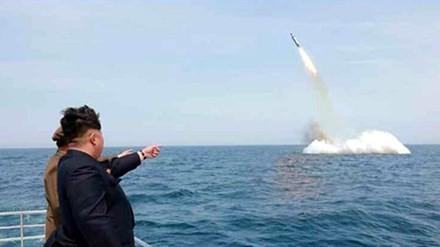 Lãnh đạo Triều Tiên Kim Jong-un chỉ tay vào một tên lửa đạn đạo được cho là phóng từ dưới nước. Ảnh: KCNA/EPA.