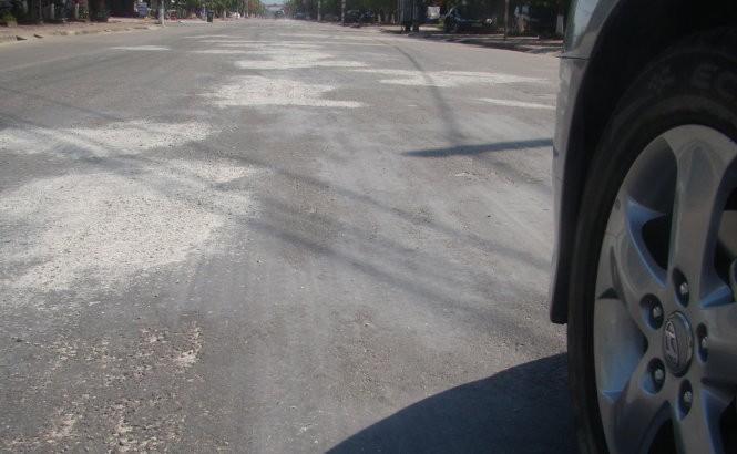 Bột đá xay được rải lên những đoạn đường bị chảynhựa tránh gây nguy hiểm cho xe cộ qua lại- Ảnh: Văn Định