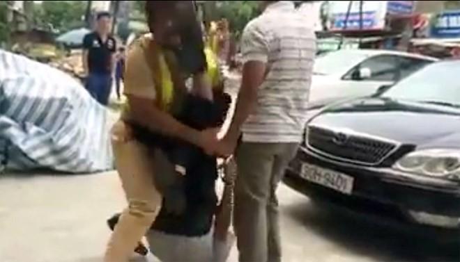 Hà Nội: Cảnh sát giao thông bị giật tung áo, rớt súng xuống đường - ảnh 1