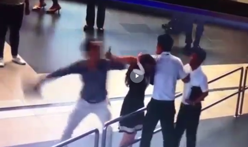 Hành khách dùng máy tính bảng đánh vào đầu nữ nhân viên. Ảnh cắt từ clip sân bay Nội Bài