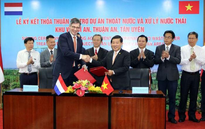 Ông Trần Thanh Liêm (phải), Chủ tịch UBND tỉnh Bình Dương và Tổng lãnh sự Cộng hòa Hà Lan tại TP.HCM hoàn thành nghi thức ký kết tài trợ. Ảnh: HL